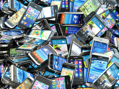 Mobile phones background. Pile of different modern smartphones.